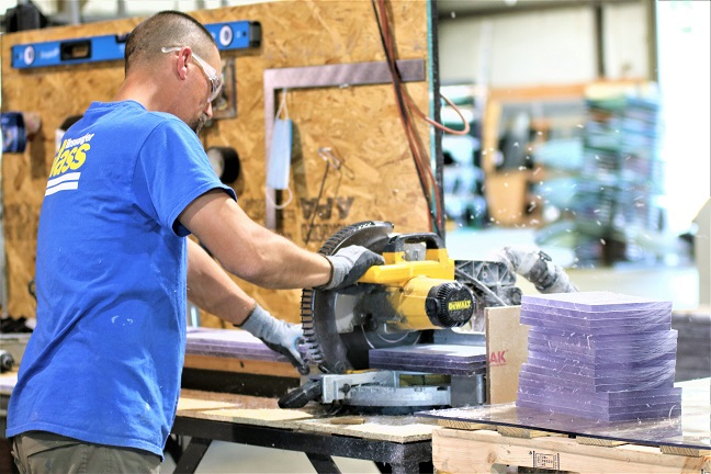 A worker at Bizwanger Glass in Topeka making plexiglass shields to protect voters and poll workers from the coronavirus. (Photo by Jim McLean / Kansas News Service)