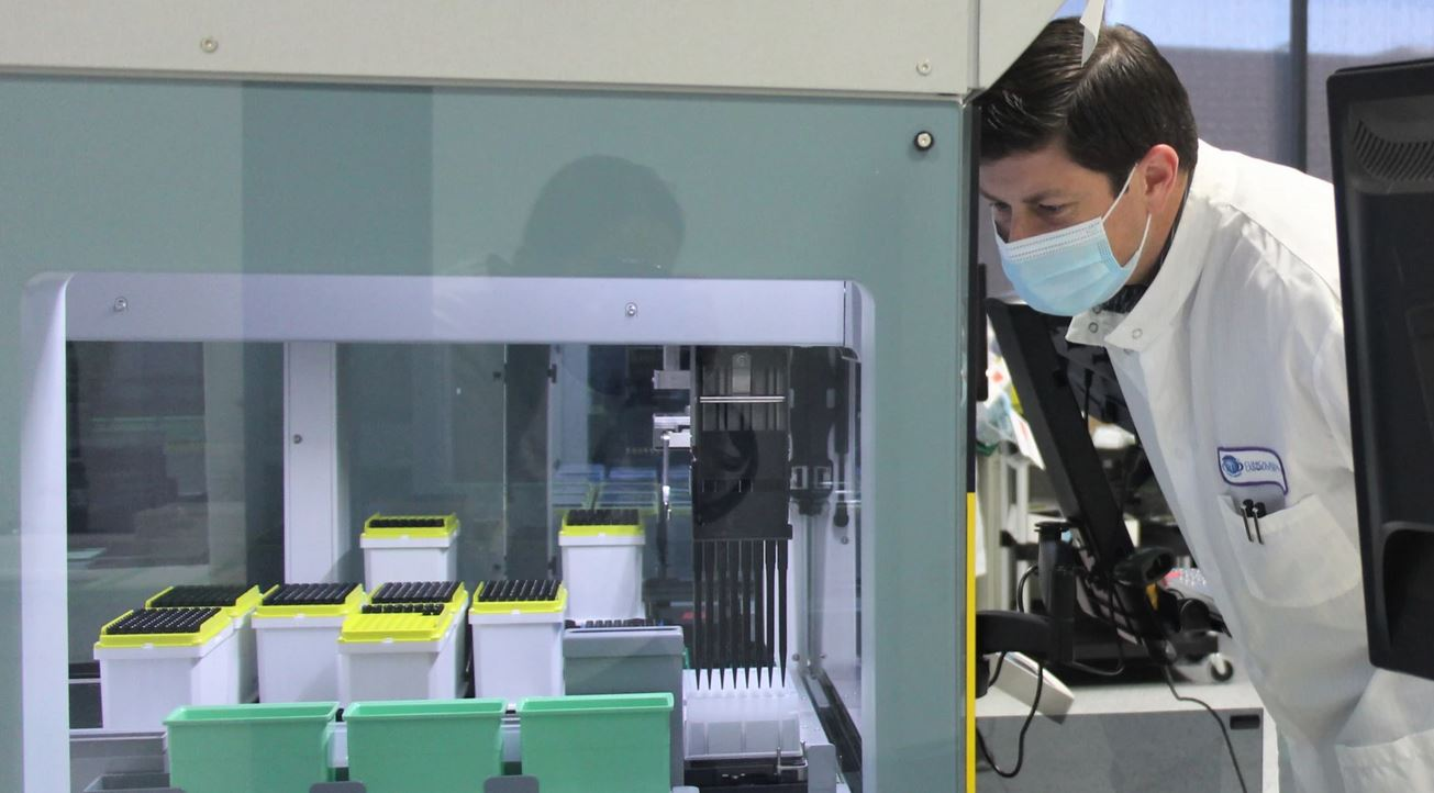 The liquid-handling robots at CRL in Lenexa have been hard to get since the pandemic hit. They can work on saliva from dozens or even hundreds of people at once. (Photo by Celia Llopis-Jepsen, Kansas News Service)