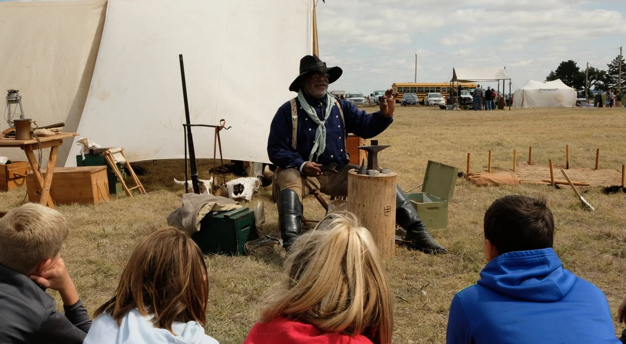 Henry Crawford demonstrates to Wallace County schoolkids during a field trip in September how to load the antique cartridges once used for buffalo hunting on the Kansas plains. (Photo by Esther Honig)