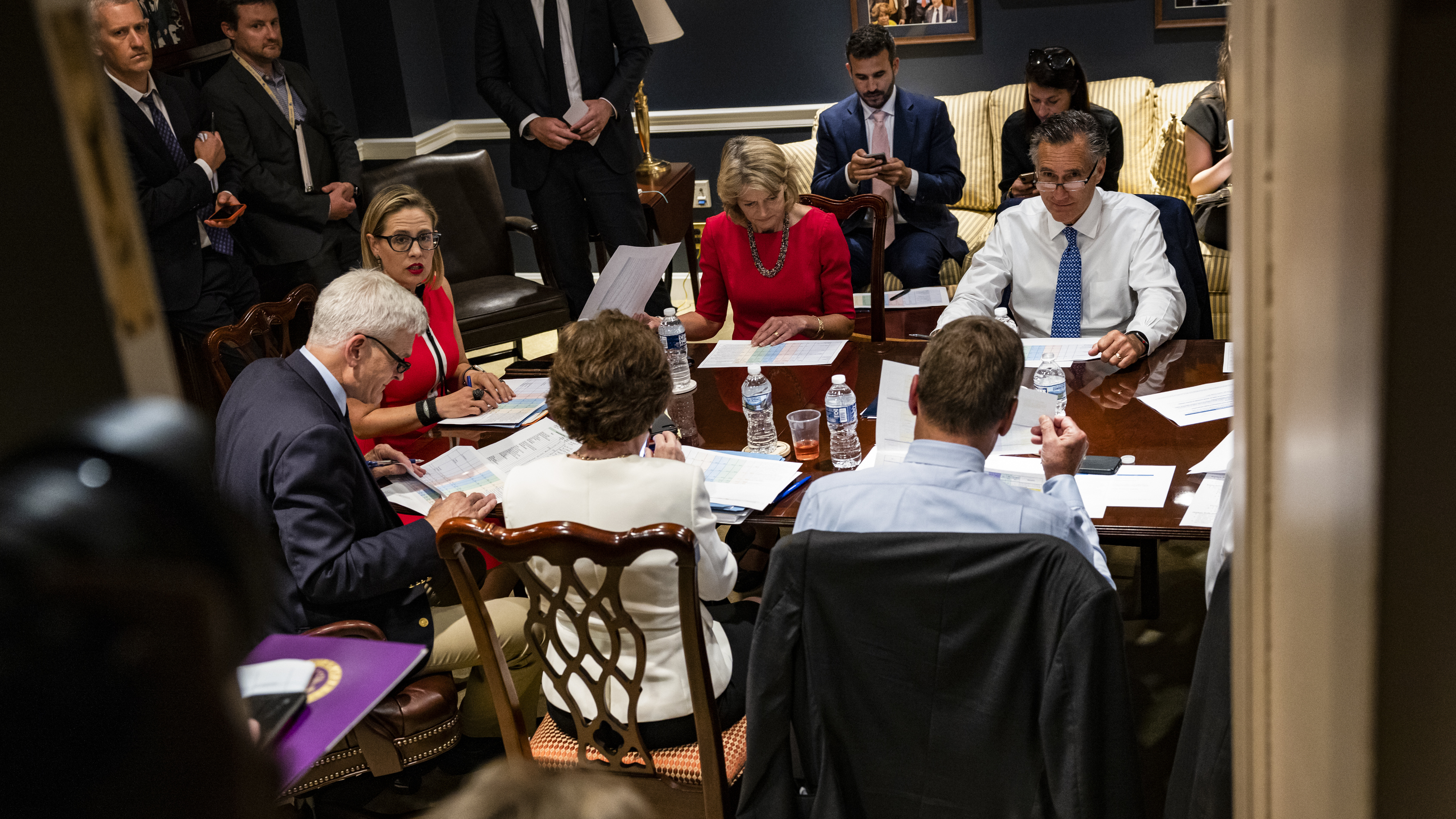 From left: Sens. Bill Cassidy, R-La., Kyrsten Sinema, D-Ariz., Lisa Murkowski, R-Alaska, Mitt Romney, R-Utah, and others hold a bipartisan meeting on infrastructure in the basement of the U.S. Capitol on Tuesday.