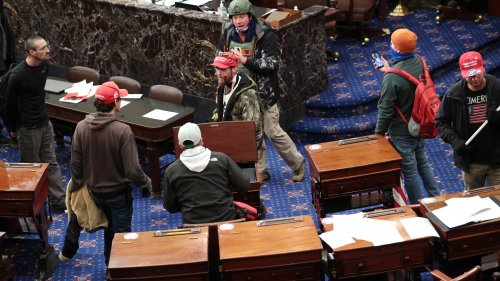 Bruno Cua, 18, is allegedly seen here with his back to the camera, holding a tan jacket. Prosecutors say he entered the Senate Chamber of the U.S. Capitol on Jan. 6 with a handful of other rioters.