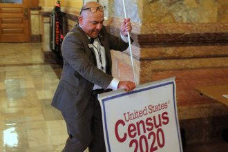 Carlos Urquilla-Diaz takes down a sign after a news conference at the Kansas Statehouse on Wednesday. He's a partnership specialist with the U.S. Census and is traveling the state to talk about the importance of the count. (Photo by Stephen Koranda)