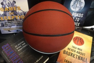 Photo of basketball in foreground, four books in background.