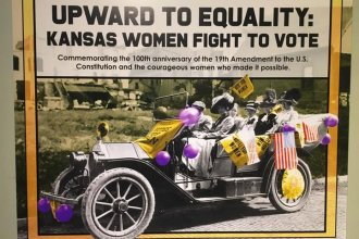 """Image of suffragettes in car under banner """"Upward to Equality"""""""