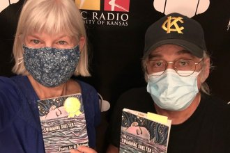 Photo of Kaye McIntyre and Al Ortolani standing in front of KPR backdrop