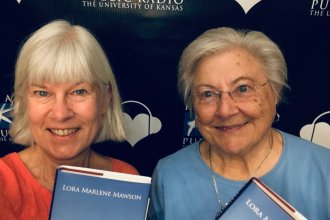 Photo of Kaye McIntyre and Marlene Mawson with books, KPR background