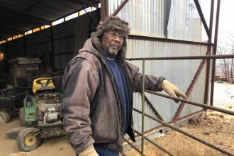 Alvin Lee stands beside his barn on his 160-acre farm near Wewoka, Oklahoma. (Photo by Seth Bodine / Harvest Public Media)
