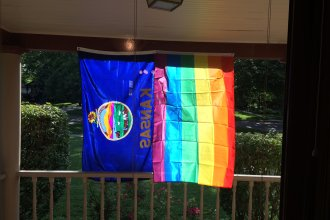 The Kansas state flag and the gay pride flag, hanging from the porch of William Jennings Bryan Oleander's home in Here, Kansas. (Photo by WJB Oleander)