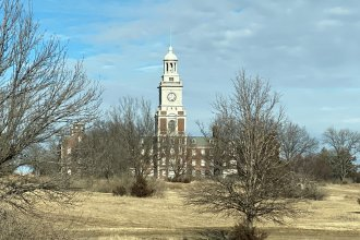 Menninger clock tower building, partially obscured by trees. (Photo courtesy of the Sunflower Foundation)