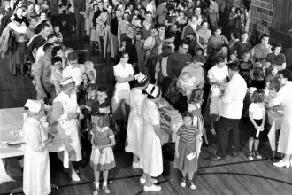 A crowd of people receives inactivated poliovirus vaccine (the Salk vaccine) in the high school gym at Protection, Kansas, in 1957. The small southwest Kansas town became the first in the nation to be fully-immunized against polio. Similar lines formed during the 1954 vaccine field trials. (Photo via March of Dimes Foundation)