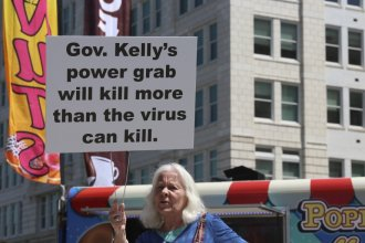 A protester outside the Kansas Statehouse in the spring of 2020. (Photo from Kansas News Service)