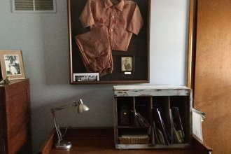 Above the desk in Rex Buchanan's home office, hangs a framed Saxman, Kansas, baseball uniform worn by his grandfather.  (Photo by Mindy James)
