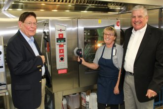 Generals Edward Gerhardt (left) and Daryl McCall tour the upgraded kitchen facilities at Hillcrest Elementary in Lawrence, Kan. General Gerhardt is from the tiny town of Netawaka in northeast Kansas. (Photo by J. Schafer)
