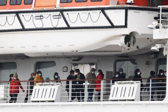 Passengers walk along the deck of the Diamond Princess cruise ship, on which about 3,600 people have been quarantined because of fears of the new COVID-19 coronavirus.