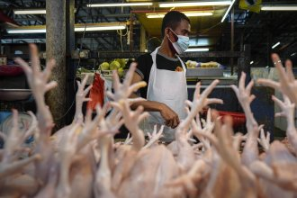 A poultry vendor wearing a face mask to help curb the spread of the coronavirus prepares birds at a wet market in downtown Kuala Lumpur, Malaysia, in April.