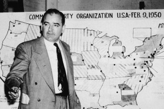 Sen. Joe McCarthy, R-Wis., testifies during hearings in Washington, D.C., on June 9, 1954. McCarthy stands before a map that charts alleged communist activity in the United States.