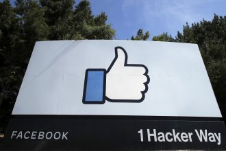"""In this April 14, 2020 file photo, the thumbs up """"like"""" logo is shown on a sign at Facebook headquarters in Menlo Park, Calif. Facebook says it plans to hire 10,000 workers in the European Union over the next five years to work on a new computing platform."""