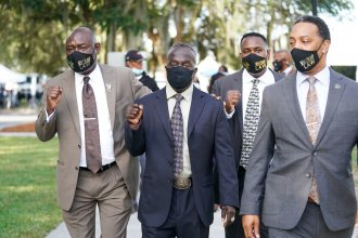 Attorney Ben Crump, left, and Marcus Arbery Sr., the father of Ahmaud Arbery, second from left, arrive at the Glynn County Courthouse in Brunswick, Ga., as jury selection begins for the trial of the shooting death of Ahmaud Arbery on Monday.