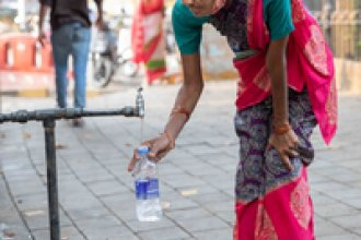 A woman fills a bottle from the tap at the Seth Gangalal V. Mulji Nandlal fountain. Researchers and water rights activist say the pandemic has exacerbated the huge inequality in Mumbai's water supply, with lower-income families struggling to find affordable and safe water.