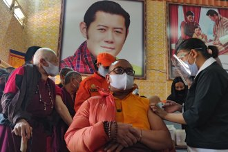 A health worker vaccinates a Buddhist monk sitting in front of a portrait of Bhutanese King Jigme Khesar Namgyel Wangchuck at a secondary school in Bhutan on March 27, the first day of the country's vaccination campaign. Less than two weeks later, health officials said 93% of eligible adults had received their first dose of a COVID-19 vaccine.