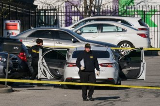 Crime scene investigators walk through the parking lot of a FedEx facility in Indianapolis on Friday. A gunman killed at least eight people and injured several others.