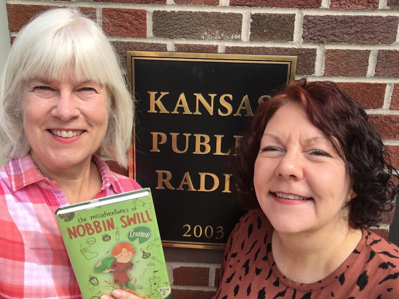 Photo of Kaye McIntyre and Lisa Harkrader holding copy of book, KPR sign in background